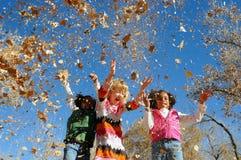 Mädchen, die mit Blättern spielen stockfoto