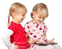 Mädchen, die mit einem Tablettecomputer spielen stockbilder