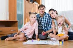 Mädchen, die mit Eltern am Brettspiel auf Boden spielen Stockfotos