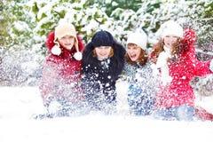 Mädchen, die mit Schnee im Park spielen Stockfotografie