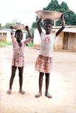 Mädchen, die Schüsseln auf ihrem Kopf tragen Lizenzfreies Stockfoto