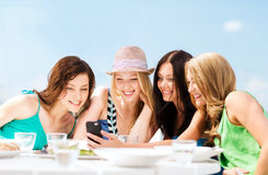 Mädchen, die Smartphone im Café auf dem Strand betrachten Stockfotografie