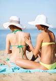 Mädchen, die Sonnencreme auf dem Strand auftragen Stockbilder