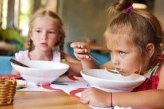 Mädchen, die Suppe essen stockbild