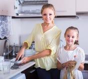Mädchen, die Teller in der Küche tun und abwischen Lizenzfreies Stockfoto