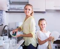 Mädchen, die Teller in der Küche tun und abwischen Stockfotografie