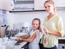 Mädchen, die Teller in der Küche tun und abwischen Stockfoto