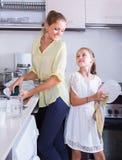 Mädchen, die Teller in der Küche tun und abwischen Lizenzfreie Stockbilder