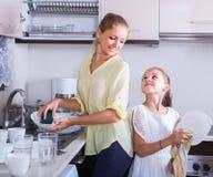 Mädchen, die Teller in der Küche tun und abwischen Stockbild