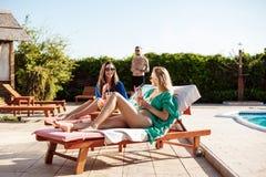 Mädchen, die, trinkende Cocktails, Ein Sonnenbad nehmen, liegend nahe Swimmingpool lächeln Stockfoto