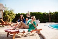 Mädchen, die, trinkende Cocktails, Ein Sonnenbad nehmen, liegend nahe Swimmingpool lächeln Stockbild