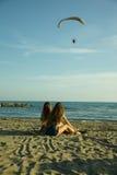 Mädchen, die vor dem Ozean in entspannendem breitem Schuss des Sommers sitzen Lizenzfreie Stockfotos
