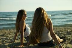 Mädchen, die vor dem Ozean im Entspannungsc$lachen des Sommers sitzen Lizenzfreies Stockbild