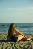 Mädchen, die vor dem Ozean im Sommer entspannend sitzen Lizenzfreie Stockbilder