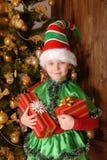 Mädchen - die Weihnachtselfe mit einem Geschenk Stockbild