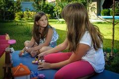 Mädchen, die whith Puppen im Sommer spielen Lizenzfreies Stockbild