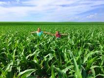Mädchen, die wie Vogelscheuchen auf dem Maisgebiet fungieren Lizenzfreies Stockbild