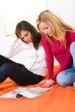 Mädchen, die Zeitschrift durchstöbern Stockbild