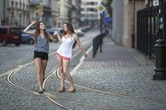 Mädchen, die zusammen auf die Pflasterung auf der Straße gehen Stockfotografie