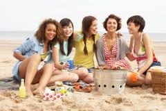 Mädchen, die zusammen Grill auf Strand genießen Stockbilder