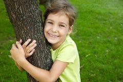 Mädchen, dieses Standplätze, Baum im Park umfassend Stockbild