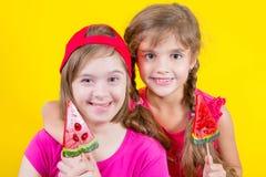 Mädchen Down-Syndrom und kleines Mädchen mit großem Lutscher Stockfotografie