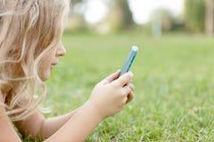 Mädchen draußen mit einem Handy Stockfotos