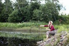 Mädchen durch den Fluss mit einer Angelrute stockbilder