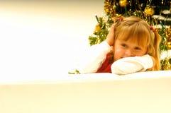 Mädchen durch Weihnachtsbaum Stockbild