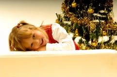 Mädchen durch Weihnachtsbaum Stockfotografie