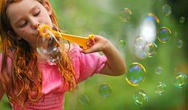 Mädchen-durchbrennenluftblasen draußen Lizenzfreie Stockbilder