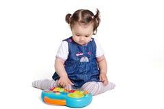 Mädchen ein Jahr, das mit einem musikalischen Spielzeug spielt Lizenzfreie Stockfotos