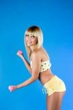 Mädchen eine in den Gelbholding Dumbbells auf einem Blau Lizenzfreies Stockfoto