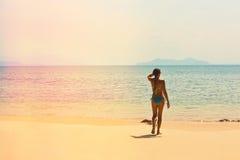 Mädchen in einem Badeanzug auf dem leeren tropischen Strand Stockbild