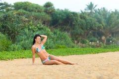 M?dchen in einem Badeanzug, der auf dem Strand Sri Lanka aufwirft ?berraschendes M?dchen in einem wei?en Badeanzug mit einer sch? lizenzfreies stockbild