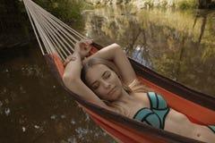 Mädchen in einem Badeanzug, der in einer Hängematte über dem Wasser liegt Stockfotografie