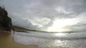 Mädchen in einem Badeanzug läuft entlang den Strand bei Sonnenuntergang in der Zeitlupe, Bali stock video footage