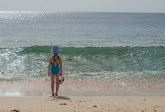 Mädchen in einem Badeanzug steht und betrachtet den Ozean Stockfotografie