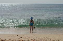 Mädchen in einem Badeanzug steht und betrachtet den Ozean Lizenzfreies Stockbild