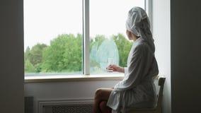 Mädchen in einem Bademantel und in einem Tuch auf Hauptsitzen stock footage