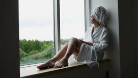 Mädchen in einem Bademantel und in einem Tuch auf Kopf sitzt auf dem Fenster stock video