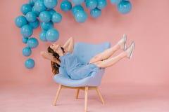 Mädchen in einem blauen Kleid in einem rosa Raum mit einem blauen Stuhl und einem blauen b lizenzfreie stockfotografie