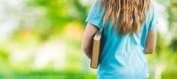 Mädchen in einem blauen T-Shirt, das ein Buch hält Lizenzfreies Stockbild