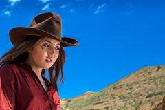 Mädchen in einem Cowboyhut auf einem Hintergrund von Bergen lizenzfreies stockbild