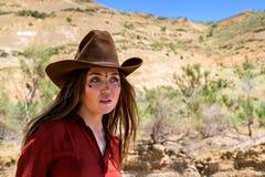 Mädchen in einem Cowboyhut auf einem Hintergrund von Bergen stockfotografie