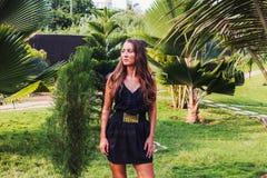 Mädchen in einem eleganten Kleid gegen einen Hintergrund von Palmen lizenzfreie stockfotos