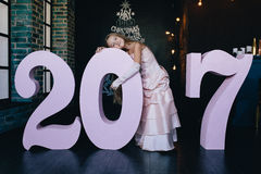 Mädchen in einem festlichen Kleid, das mit großen Nr. 2017 steht Guten Rutsch ins Neue Jahr-Konzept 2017 Stockfotografie