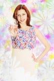 Mädchen in einem geblühten Kleid, das eine Flasche Parfüm hält Lizenzfreies Stockfoto