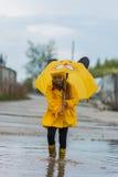 Mädchen in einem gelben Kleid mit einem frohen Frühling des Regenschirmes läuft durch die Pfützen an einem regnerischen Tag lizenzfreie stockbilder