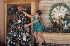 Mädchen in einem grünen Kleid nahe einem Weihnachtsbaum Lizenzfreies Stockbild